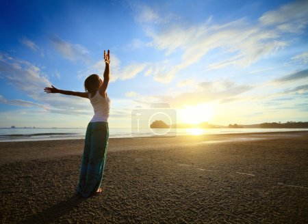 Photo for Young woman with raised hands standing on sand and looking to a sky - Royalty Free Image