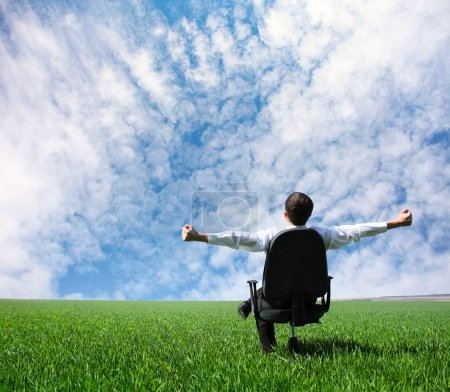 Photo for Man with raised hands sitting on chair on green meadow - Royalty Free Image