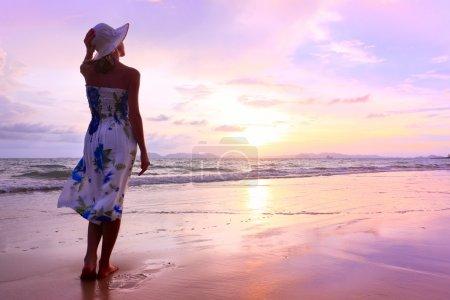 Photo pour Jeune femme en chapeau de paille debout sur du sable humide et regardant quelque part - image libre de droit