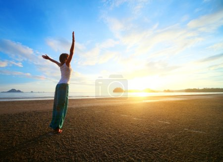 Photo for Young woman with raised hands standing on wet sand and looking to a sky - Royalty Free Image