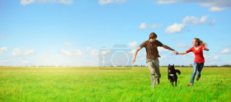 Photo for Young happy lovers runnung with a dog on meadow with green grass and blue sky - Royalty Free Image