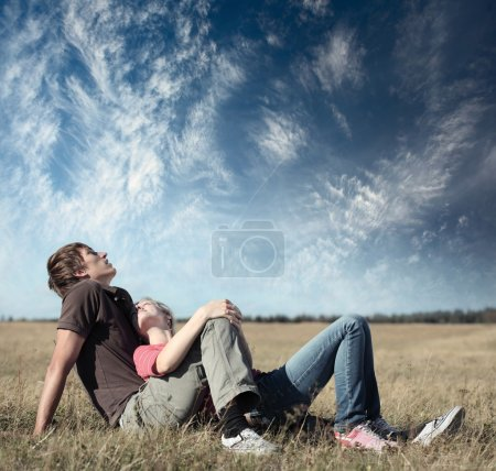 Young happy lovers lying on meadow on blue sky background
