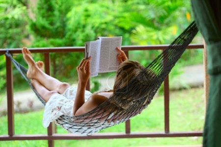 Photo for Young woman reading a book lying in hammock - Royalty Free Image