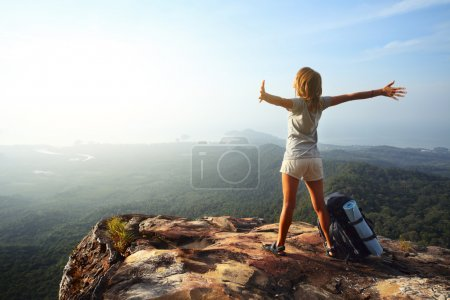 Photo for Young woman with backpack standing on cliff's edge and looking to a sky with raised hands - Royalty Free Image