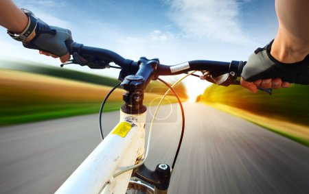 Photo for Hands in gloves holding handlebar of a bicycle. Motion blurred asphalt road - Royalty Free Image