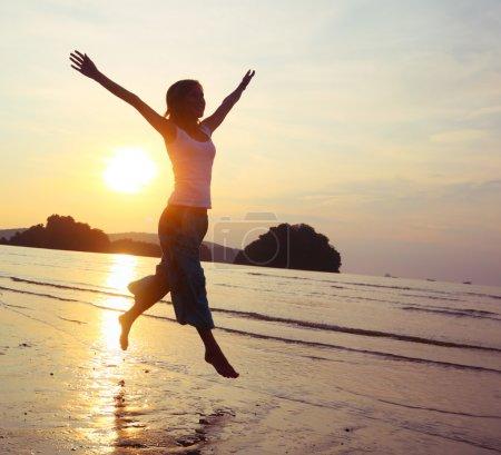 Photo pour Jeune femme avec les mains levées courant sur le sable mouillé - image libre de droit