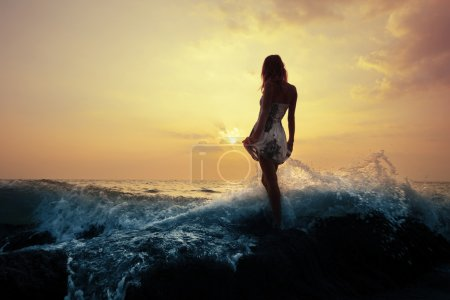 Photo for Young woman standing on a rock in sea and holding her dress. Toned - Royalty Free Image