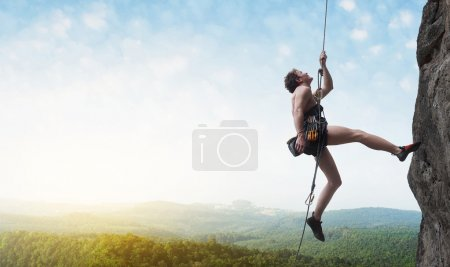 Photo for Young male climber hanging by a cliff on wide alley background - Royalty Free Image