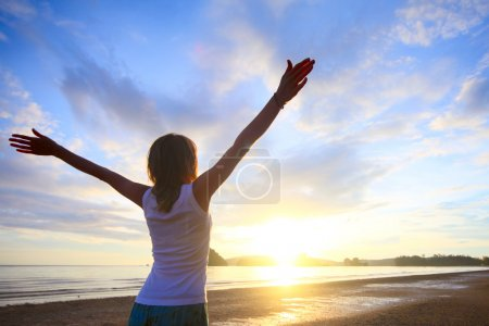 Photo for Young woman with raised hands standing on wet sand and looking to a horizon - Royalty Free Image