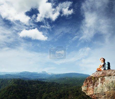 Photo pour Jeune femme avec sac à dos assis sur le bord de la falaise et regardant vers un ciel - image libre de droit