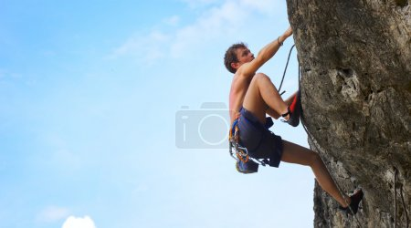 Photo for Young male climbing on a cliff on blue cloudy sky background - Royalty Free Image
