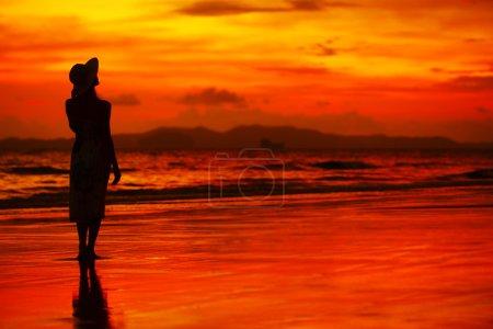 Photo pour Jeune femme en chapeau debout sur du sable mouillé et regardant vers le ciel du coucher de soleil rouge - image libre de droit