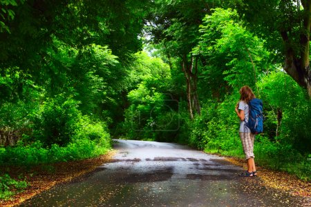 Photo for Young woman with backpack standing on a wet asphalt path in a park and looking to a trees - Royalty Free Image
