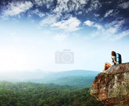Photo for Young woman with backpack sitting on cliff and looking to a sky - Royalty Free Image
