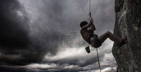 Photo for Young man hanging on a rope by a cliff - Royalty Free Image
