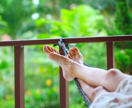 Photo for Feet of a young woman lying in hammock in a garden - Royalty Free Image