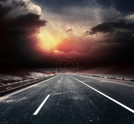 Photo for Dirty asphalt road and dark thunder clouds - Royalty Free Image