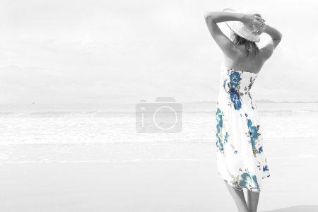 Photo pour Jeune femme debout sur une plage et regardant vers l'horizon. Version incolore avec robe partiellement tonique - image libre de droit