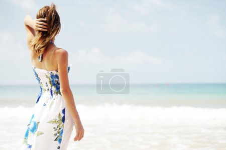 Photo for Young woman in summer dress standing by blue sea and looking to horizon - Royalty Free Image