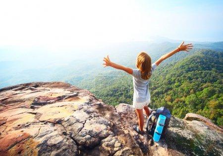 Photo pour Jeune femme debout avec sac à dos sur le bord de la falaise et de la recherche dans une large vallée - image libre de droit