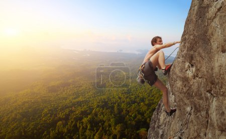 Photo for Young man climbs on a rocky wall in a valley with mountains at sunrise - Royalty Free Image