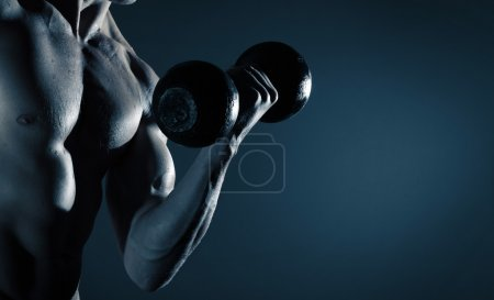 Photo for Part of a man's body with metal dumbbell on a gray background - Royalty Free Image