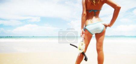 Photo pour Jeune femme debout de peau mouillée avec masque et tuba en mer d'un bleu et aller nager - image libre de droit
