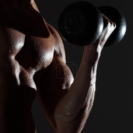 Photo for Part of a wet man's body with metal dumbbell on a gray background - Royalty Free Image
