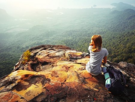 Photo for Young woman sitting on a rock with backpack and looking to the horizon - Royalty Free Image