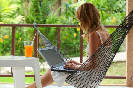 Photo for Young woman sitting in a hammock in a garden and typing something on a laptop - Royalty Free Image