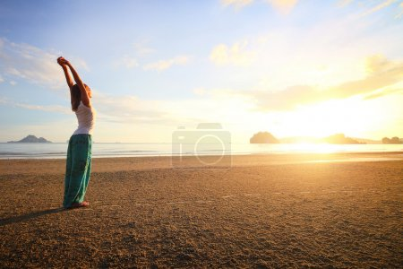 Photo for Young woman standing on a sandy beach - Royalty Free Image