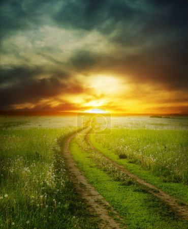 Photo for Road in field under dramatic sunset light - Royalty Free Image