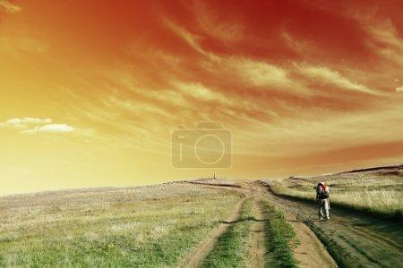 Photo pour Randonneur marchant sur la route sous un ciel abstrait - image libre de droit