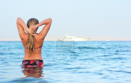 Photo for Alone woman standing in sea water and looking to horizon - Royalty Free Image