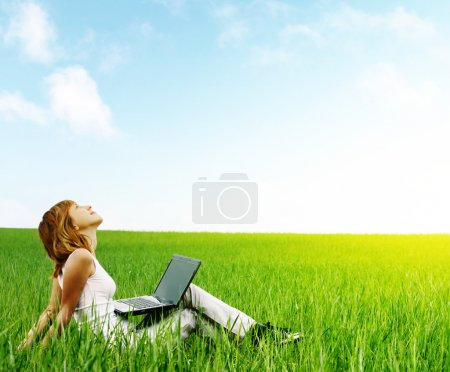 Photo for Young smiling woman with laptop sitting in meadow with green grass - Royalty Free Image