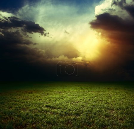 Photo for Storm dark clouds over field with grass - Royalty Free Image