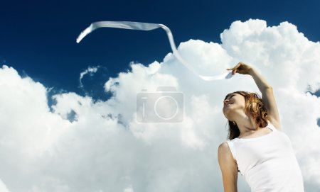 Photo for Young woman in white shirt with ribbon over blue sky with fluffy clouds - Royalty Free Image