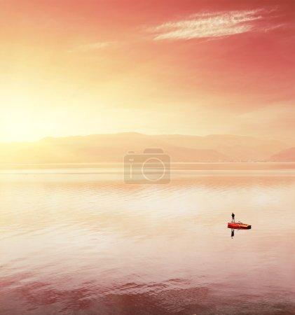 Photo pour Seul pêcheur en bateau sur un lac énorme sous la lumière de la rangée - image libre de droit