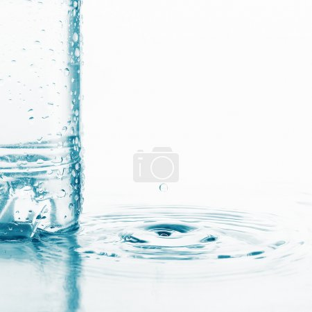 Photo for Plastic wet bottle with water and little drop with ripples on water surfase - Royalty Free Image