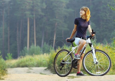 Photo for Young woman on bike standing on road and looking to somewhere - Royalty Free Image