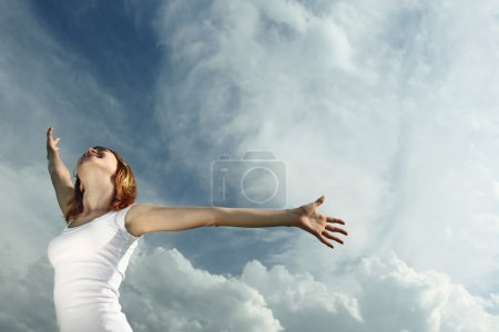 Photo for Woman in white with raised hands over airy sky backgroud - Royalty Free Image