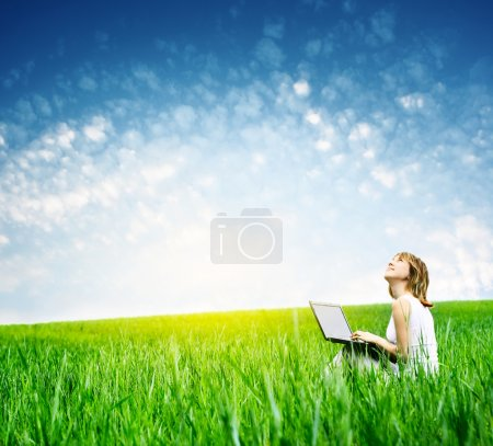 Photo for Young woman with laptop sitting on green grass and looking to a sky - Royalty Free Image