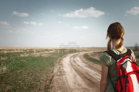 Photo for Young woman with backpack on rural road looking to somewhere - Royalty Free Image