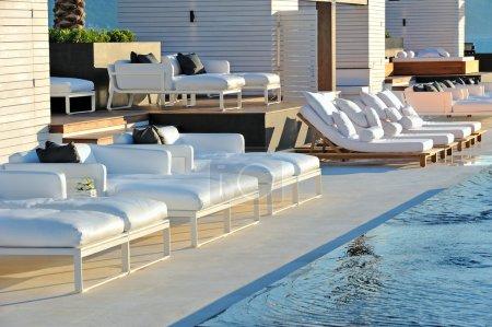 Photo pour Partie de l'aire de loisirs de l'hôtel avec piscine et chaises longues - image libre de droit