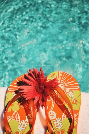 Photo for Flip Flops on white towel by swimming pool - Royalty Free Image