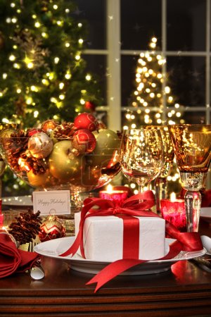 Photo for Festive dinner table setting with red ribbon gift - Royalty Free Image