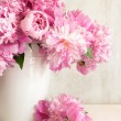 Pink peonies in vase on wood background...