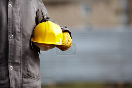 Photo for Hand of builder with yellow hardhat, natural light,selective focus - Royalty Free Image