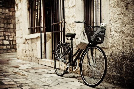 Photo for Old bicycle with basket and shopping bag, parked in the narrow cobble street - Royalty Free Image