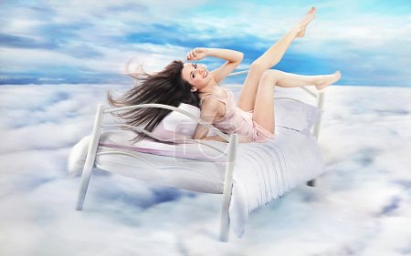 Photo for Brunette beauty lying on a bed in clouds - Royalty Free Image